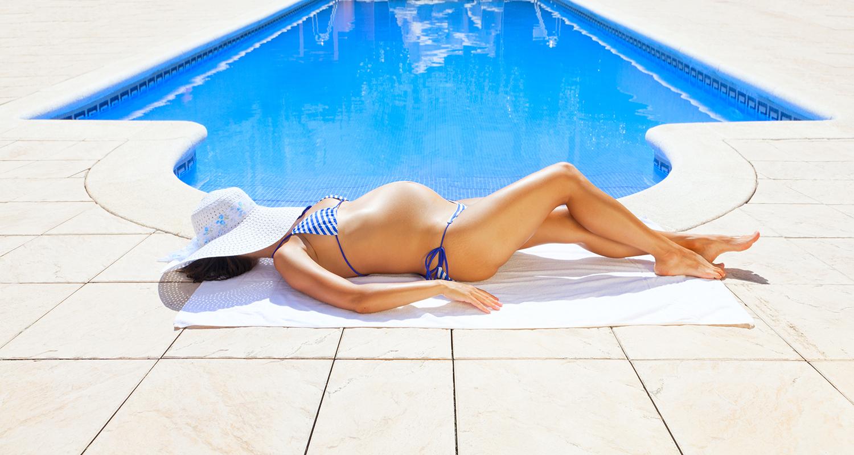 Pregnant woman sunbathing next to resort swimming pool
