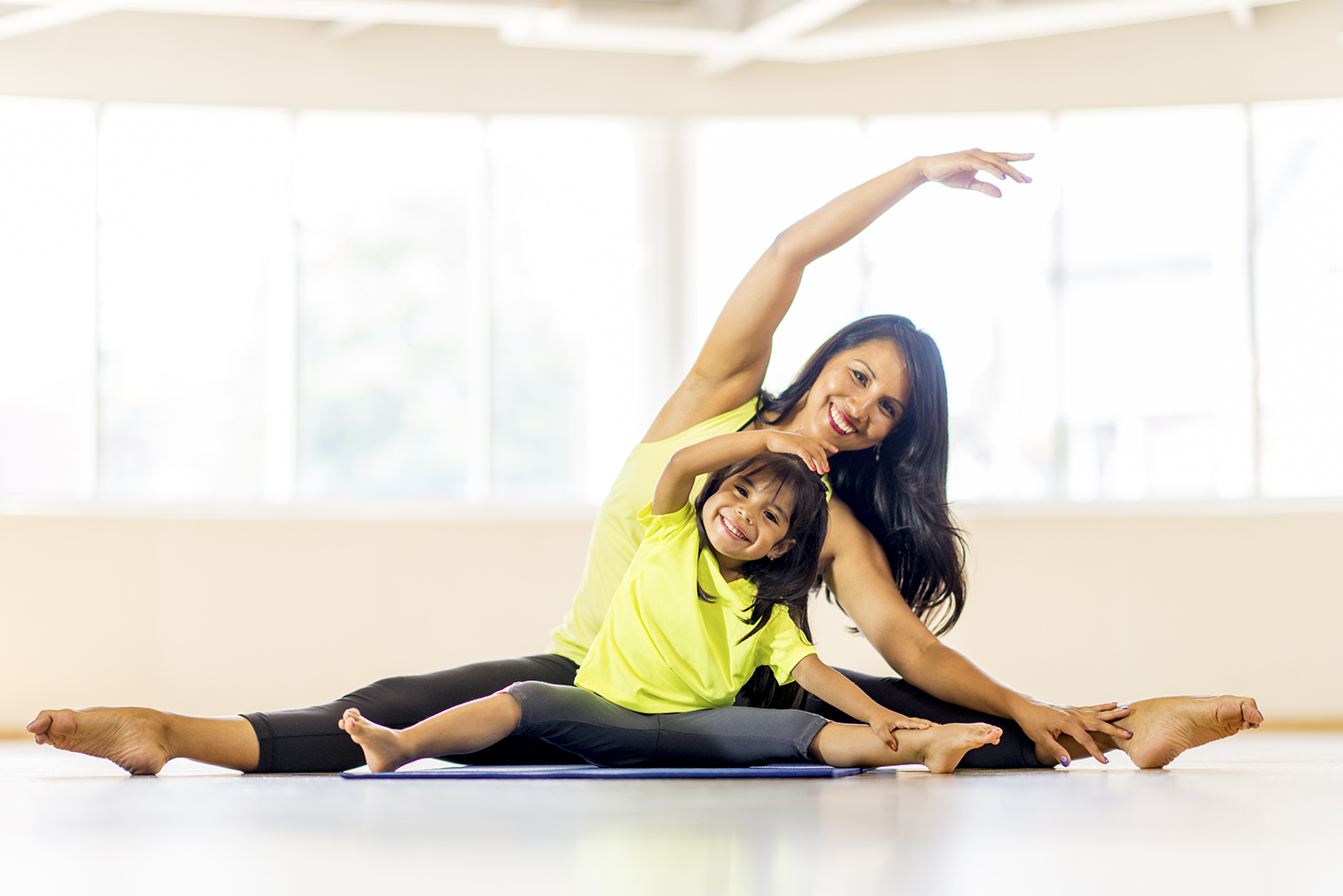 A mother and her cute little girl are stretching together during a yoga class - they are reaching their arms overhead and are stretching to their toes. They are wearing matching athletic clothing and are smiling and looking at the camera.