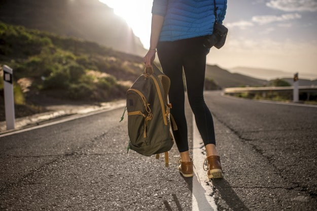 Woman hikes on the road.