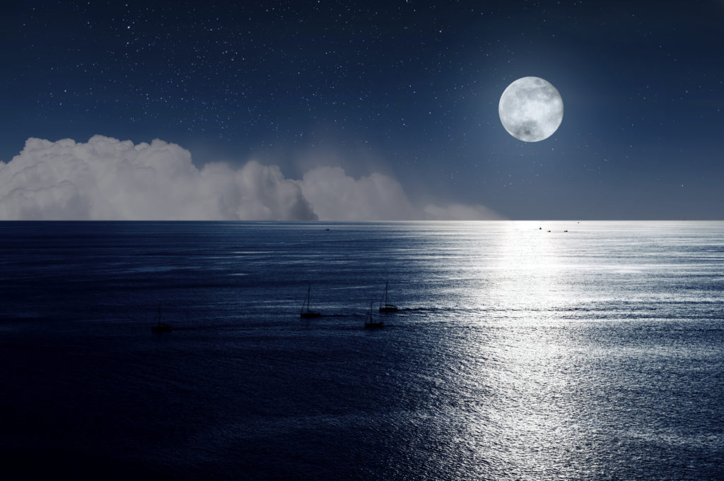 moon and clouds in the night over the ocean
