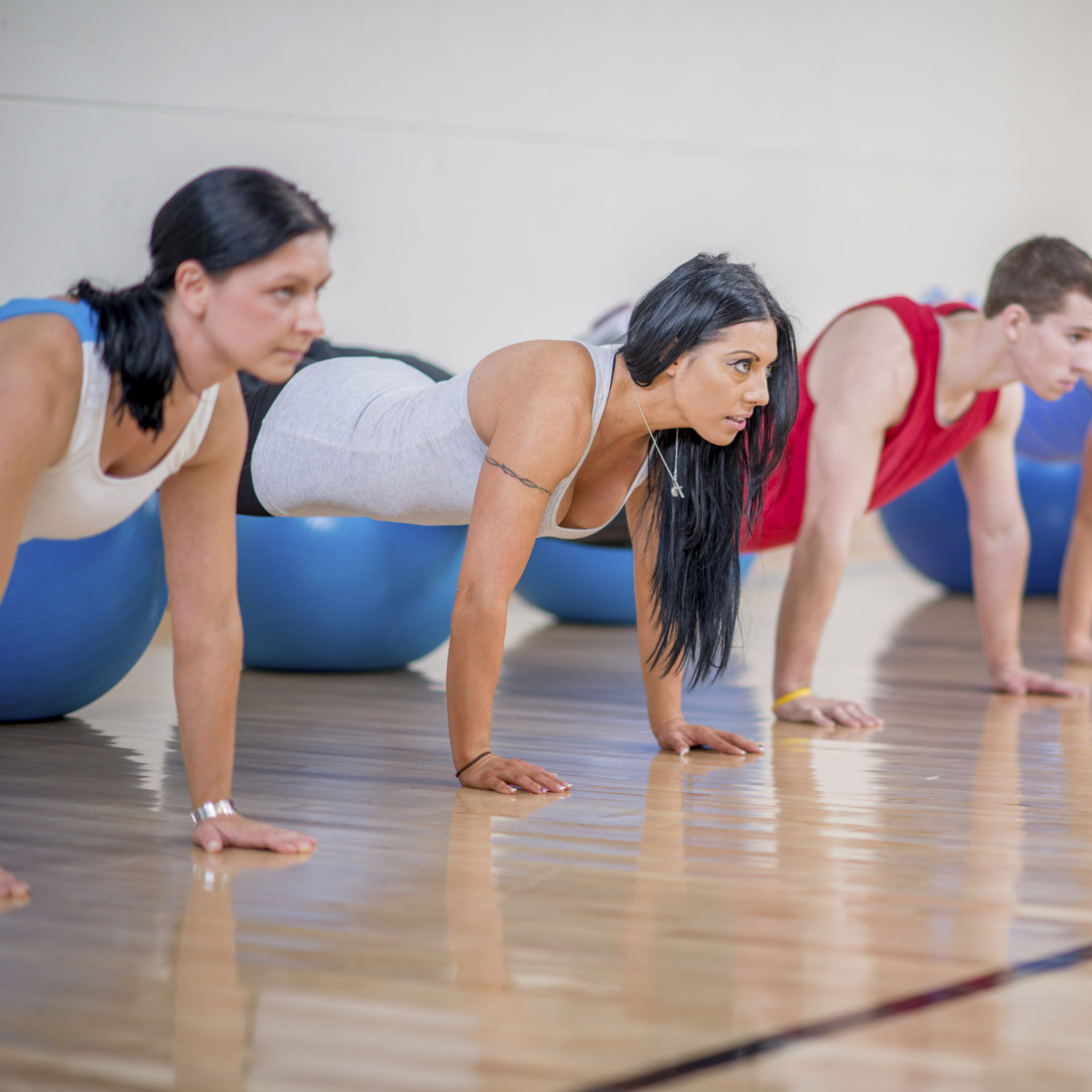 Group Doing Stability Ball Pushups at the Gym