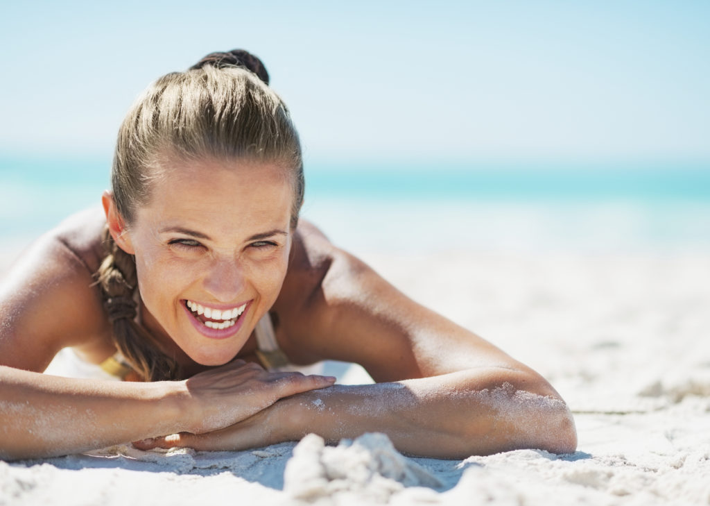 Portrait of smiling young woman in swimsuit laying on beach
