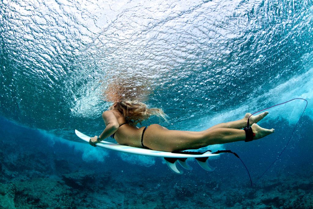 female surfer duck diving a wave