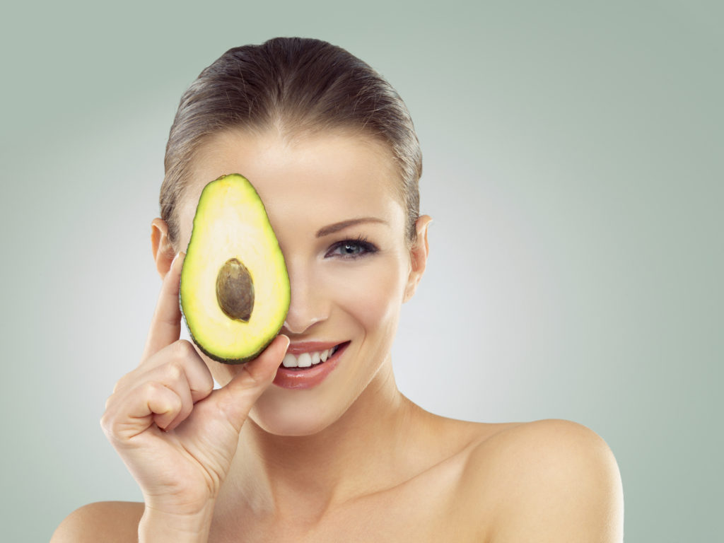 avocado being held over a woman's face