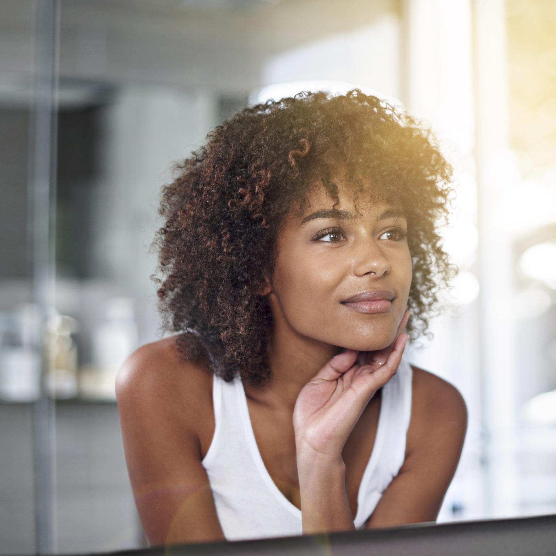 woman in mirror touching skin